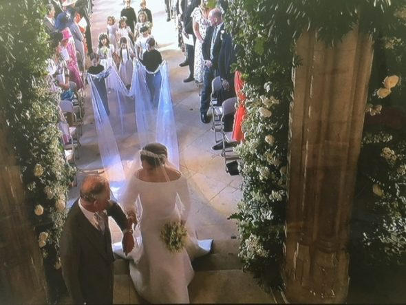 Meghan being walked half way down the aisle by the Prince of Wales. The Bridge MAG. Image